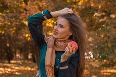 Το νέο κορίτσι που ντύνεται στο μαντίλι και τις μαύρες στάσεις σακακιών στο πάρκο κοιτάζει στη δευτερεύουσα εκμετάλλευση Apple Στοκ Εικόνες