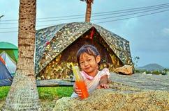 Το νέο κορίτσι προσφέρει το πορτοκαλί ποτό της σε ένα campground στοκ εικόνα με δικαίωμα ελεύθερης χρήσης