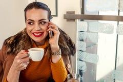 Το νέο κορίτσι σε έναν καφέ πίνει τον καφέ και την ομιλία στο smartphone Στοκ φωτογραφία με δικαίωμα ελεύθερης χρήσης