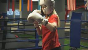 Το νέο κορίτσι σε ένα κράνος και τα γάντια εκπαιδεύει τα χτυπήματα closeup φιλμ μικρού μήκους