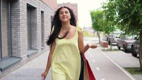 Το νέο κορίτσι σε ένα μακρύ φόρεμα πηγαίνει γύρω από την πόλη μετά από να ψωνίσει έχοντας μια καλή διάθεση 4K απόθεμα βίντεο