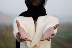 Το νέο κορίτσι σε ένα μαύρο μαντίλι κρατά τα χέρια στο θεατή Στοκ φωτογραφίες με δικαίωμα ελεύθερης χρήσης