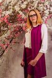 Το νέο κορίτσι σε ένα πουκάμισο και μια φανέλλα του φούξια στέκεται κοντά στο ανθίζοντας ιαπωνικό δέντρο κερασιών sakura στοκ εικόνες