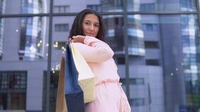 Το νέο κορίτσι σε ένα φόρεμα μετά από να ψωνίσει με τις συσκευασίες στα χέρια είναι ευχαριστημένο από τις αγορές κίνηση αργή HD απόθεμα βίντεο