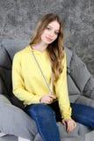 Το νέο κορίτσι σε μια φόρμα γυμναστικής κάθεται σε ένα μοντέρνο εσωτερικό στοκ εικόνες
