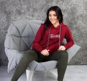 Το νέο κορίτσι σε μια φόρμα γυμναστικής κάθεται σε ένα μοντέρνο εσωτερικό στοκ εικόνες με δικαίωμα ελεύθερης χρήσης