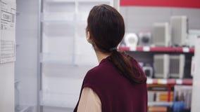 Το νέο κορίτσι σε 20 της ` s έρχεται μέχρι ένα ψυγείο στο κατάστημα συσκευών ανοίγει την πόρτα και ελέγχει έξω ποιο ` s μέσα Ανοί φιλμ μικρού μήκους