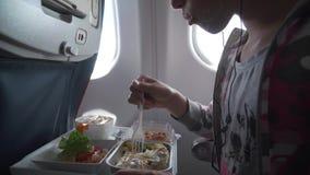 Το νέο κορίτσι στα ακουστικά τρώει το εύγευστο γεύμα στο βίντεο μήκους σε πόδηα αποθεμάτων αεροπλάνων φιλμ μικρού μήκους