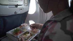 Το νέο κορίτσι στα ακουστικά τρώει το εύγευστο γεύμα στο βίντεο μήκους σε πόδηα αποθεμάτων αεροπλάνων απόθεμα βίντεο
