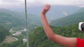Το νέο κορίτσι στα γυαλιά εικονικής πραγματικότητας ρίχνει το χέρι της επάνω άμεσα πράσινης κοιλάδας βουνών φιλμ μικρού μήκους