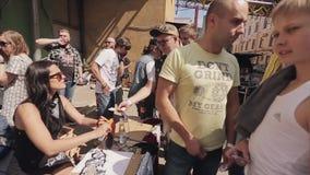 Το νέο κορίτσι στα γυαλιά ηλίου παίρνει τα χρήματα από τους ανθρώπους τους δίνει τις κάρτες χαρτοκιβωτίων θερινό ηλιόλουστο swall απόθεμα βίντεο