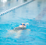 Το νέο κορίτσι στα προστατευτικά δίοπτρα που κολυμπούν πίσω σέρνεται ύφος κτυπήματος Στοκ Εικόνες