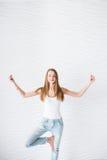 Το νέο κορίτσι στην άσπρη φανέλα και το μπλε τζιν με τις τρύπες κάνει την περισυλλογή στην άσκηση γιόγκας Στοκ Εικόνες