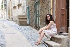 Το νέο κορίτσι στις στενές οδούς που φορούν biege ντύνει Στοκ Φωτογραφίες