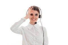 Το νέο κορίτσι στο άσπρα πουκάμισο και τα ακουστικά με το μικρόφωνο που χαμογελά κρατά το χέρι σας κοντά στα μάτια σας και την εξ Στοκ εικόνες με δικαίωμα ελεύθερης χρήσης