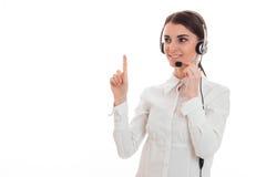 Το νέο κορίτσι στο άσπρα πουκάμισο και τα ακουστικά με το μικρόφωνο κοιτάζει μακριά και αύξησε ένα δάχτυλο επάνω Στοκ Εικόνες