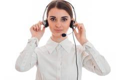 Το νέο κορίτσι στο άσπρα πουκάμισο και τα ακουστικά με το μικρόφωνο εξετάζει τη κάμερα και κρατά τα χέρια κοντά στο κεφάλι Στοκ Εικόνες
