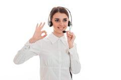 Το νέο κορίτσι στο άσπρα πουκάμισο και τα ακουστικά με το μικρόφωνο χαμογελά και παρουσιάζει χειρονομία χεριών Στοκ Εικόνες