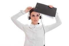 Το νέο κορίτσι στο άσπρα πουκάμισο και τα ακουστικά με το μικρόφωνο φαίνεται επάνω και αυξημένο πριν από μια ταμπλέτα Στοκ Εικόνες
