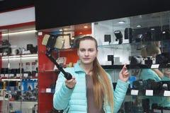 Το νέο κορίτσι στο επαγγελματικό κατάστημα εξοπλισμού φωτογραφιών καταγράφει το βίντεο στο τηλέφωνο χρησιμοποιώντας selfie το ραβ στοκ εικόνες με δικαίωμα ελεύθερης χρήσης