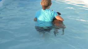 Το νέο κορίτσι στο κοστούμι λουσίματος κολυμπά στο σαφές, μπλε νερό της λίμνης με τον κόκκινο χοίρο Duroc της φυλής έτος του 2019 φιλμ μικρού μήκους