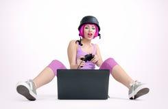 Το νέο κορίτσι στο κράνος με το πηδάλιο κάθεται στο πάτωμα και το παίζοντας παιχνίδι σε ένα lap-top Στοκ Εικόνα