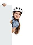 Το νέο κορίτσι στο κράνος ποδηλάτων κρατά το κάθετο άσπρο κενό, που απομονώνεται στο λευκό Στοκ Εικόνες