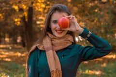Το νέο κορίτσι στο μακρύ μαντίλι κρατά τη Apple κοντά στα μάτια και χαμογελά Στοκ φωτογραφία με δικαίωμα ελεύθερης χρήσης