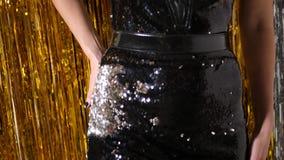 Το νέο κορίτσι στο μαύρο φόρεμα των κλιμάκων στέκεται στο υπόβαθρο χρυσό tinsel απόθεμα βίντεο