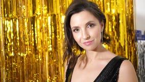 Το νέο κορίτσι στο μαύρο φόρεμα των κλιμάκων στέκεται στο υπόβαθρο χρυσό tinsel φιλμ μικρού μήκους