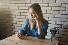 Το νέο κορίτσι στο μπλε πουκάμισο κάθεται στον πίνακα στα ακουστικά και τη σκέψη στοκ εικόνα με δικαίωμα ελεύθερης χρήσης