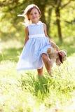 Το νέο κορίτσι στο πεδίο που φέρνει Teddy αντέχει Στοκ Εικόνες