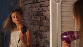 Το νέο κορίτσι στο φόρεμα χορεύει μπροστά από τον καθρέφτη ντουλαπών με το στεγνωτήρα τρίχας στα χέρια της, χαμόγελο, τραγούδι, κ φιλμ μικρού μήκους