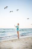 Το νέο κορίτσι ταΐζει Seagulls Στοκ Εικόνες