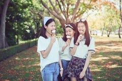 Το νέο κορίτσι τρώει το παγωτό και ευτυχής Κατά την διάρκεια της χαλάρωσης στοκ εικόνες