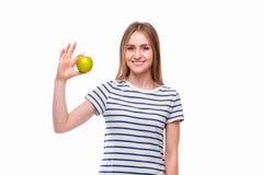 Το νέο κορίτσι τρώει το μήλο Θηλυκά δόντια και μήλο στοκ εικόνα