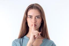 Το νέο κορίτσι φαίνεται ευθύ και τηρεί το δάχτυλο το στόμα Στοκ φωτογραφία με δικαίωμα ελεύθερης χρήσης