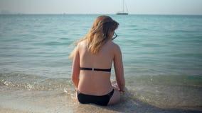 Το νέο κορίτσι φορά το μαύρο μπικίνι κάθεται σε μια αμμώδη παραλία στην ηλιόλουστη ημέρα, πίσω άποψη απόθεμα βίντεο