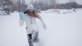 Το νέο κορίτσι χαίρεται το χειμώνα και το χιόνι, παίζει στο χειμερινό πάρκο απόθεμα βίντεο