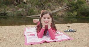 Το νέο κορίτσι χαμογελά και κύματα κάνοντας ηλιοθεραπεία σε μια παραλία ποταμών φιλμ μικρού μήκους