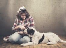 Το νέο κορίτσι χαλαρώνει με το σκυλί της στοκ φωτογραφία με δικαίωμα ελεύθερης χρήσης