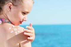 Το νέο κορίτσι applyng λιάζει την κρέμα προστάτη στον ώμο της στην παραλία κοντά στην τροπική τυρκουάζ θάλασσα κάτω από το μπλε ο Στοκ φωτογραφία με δικαίωμα ελεύθερης χρήσης