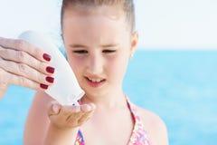 Το νέο κορίτσι applyng λιάζει την κρέμα προστάτη στον ώμο της στην παραλία κοντά στην τροπική τυρκουάζ θάλασσα κάτω από το μπλε ο Στοκ Εικόνες