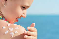 Το νέο κορίτσι applyng λιάζει την κρέμα προστάτη στον ώμο της στην παραλία κοντά στην τροπική τυρκουάζ θάλασσα κάτω από το μπλε ο Στοκ Φωτογραφία