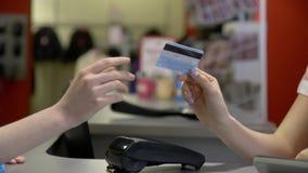 Το νέο κορίτσι brunette παρέχει μια πιστωτική κάρτα στον ταμία στο γραφείο μετρητών σε ένα πολυκατάστημα Στενό πλάνο φιλμ μικρού μήκους