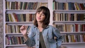 Το νέο κορίτσι brunette προσέχει στη κάμερα, που φυσά ένα φιλί, βιβλιοθήκη στο υπόβαθρο φιλμ μικρού μήκους