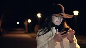 Το νέο κορίτσι Brunette σε ένα καπέλο και το λευκό παλτό ελέγχουν το τηλέφωνο και τα χαμόγελά της σε ένα πάρκο νύχτας απόθεμα βίντεο