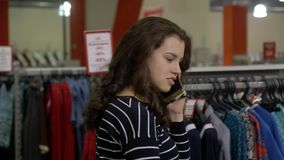 Το νέο κορίτσι brunette ψωνίζει για τα φορέματα μιλώντας στο τηλέφωνο σε ένα πολυκατάστημα φιλμ μικρού μήκους