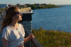 Το νέο κορίτσι eyeglasses απολαμβάνει το ηλιοβασίλεμα στην προκυμαία Στοκ φωτογραφίες με δικαίωμα ελεύθερης χρήσης
