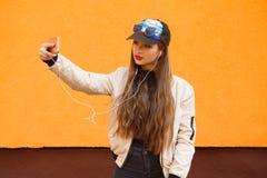 Το νέο κορίτσι hipster ομορφιάς στην ΚΑΠ και τα γυαλιά ηλίου κάνουν selfie από το smartphone και ακούνε μουσική από τα ακουστικά  Στοκ Φωτογραφία